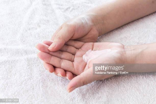 cropped hands holding cream - hand cream stock photos and pictures