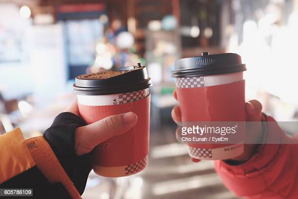 Cropped Hands Holding Disposable Coffee Cups