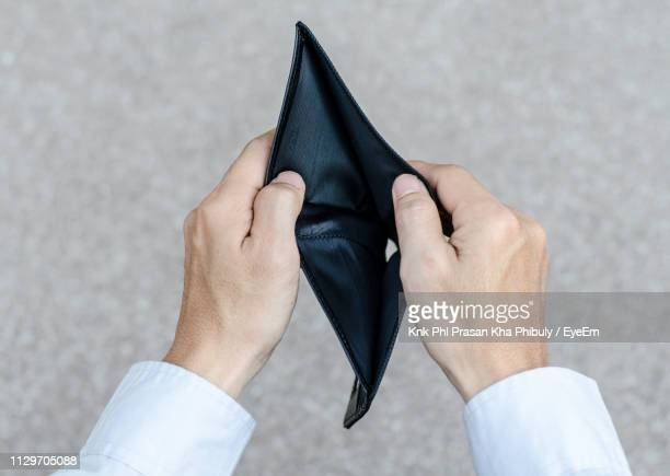 Cropped Hands Holding Empty Wallet On Road