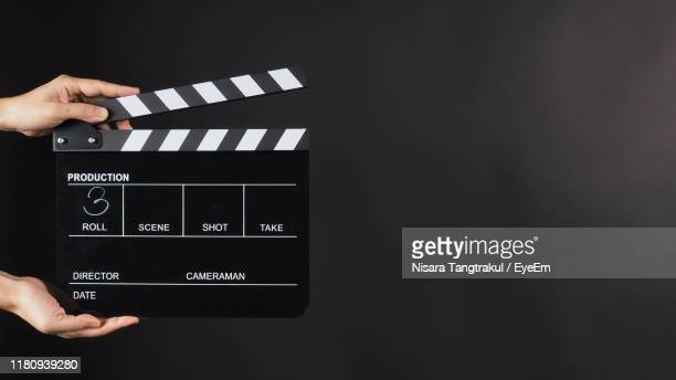 cropped hands holding film slate against black background - clapboard stock pictures, royalty-free photos & images