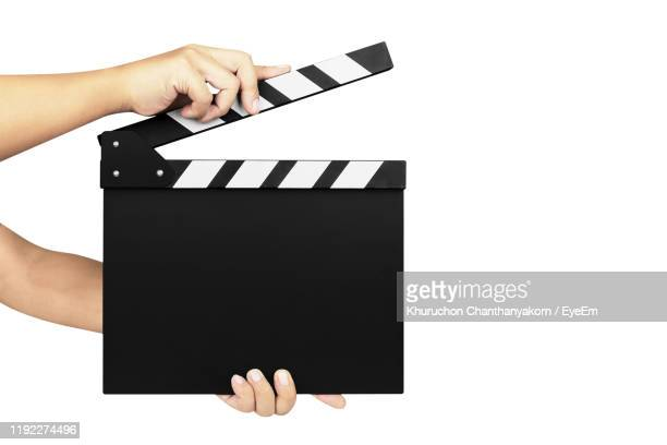 cropped hands holding film slate against white background - clapboard stock pictures, royalty-free photos & images