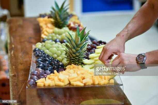 Cropped Hands Holding Fruits On Table