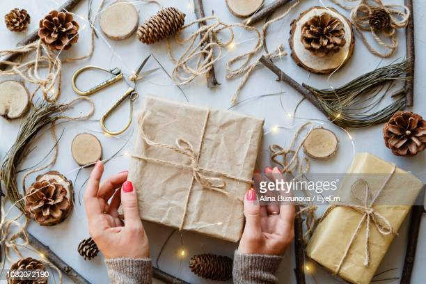 Cropped Hands Holding Gift By Christmas Decorations On Table