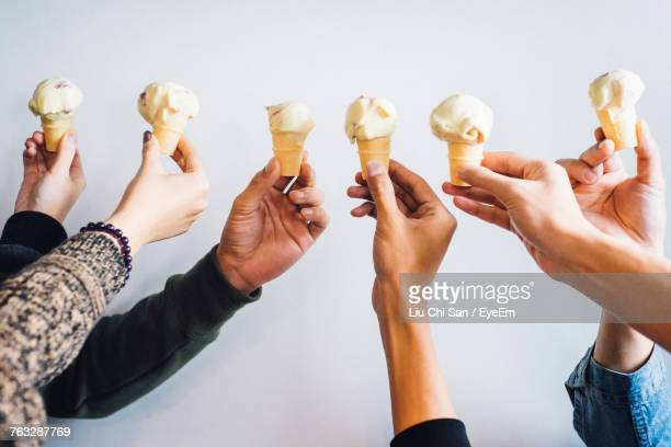 Cropped Hands Holding Ice Cream Cones Over White Background