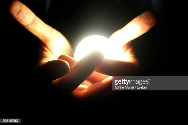 Cropped Hands Holding Illuminated Light Bulb Over Black Background