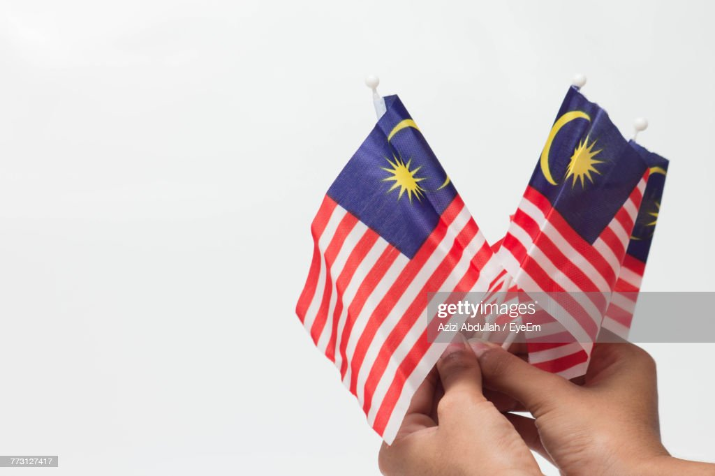Cropped Hands Holding Malaysian Flags Against Clear Sky : Stock Photo