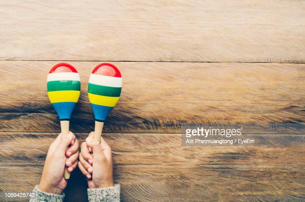 cropped hands holding maraca over table - maraca stock photos and pictures
