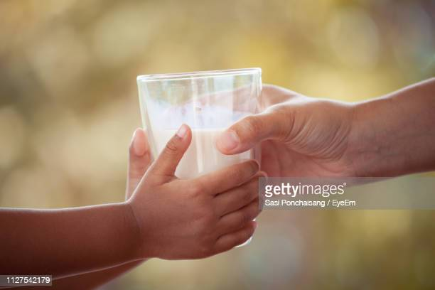 cropped hands holding milk glass - milk stock pictures, royalty-free photos & images