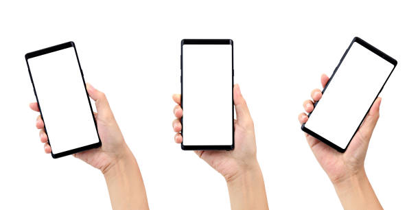 cropped hands holding mobile phones over white background - human hand stock pictures, royalty-free photos & images