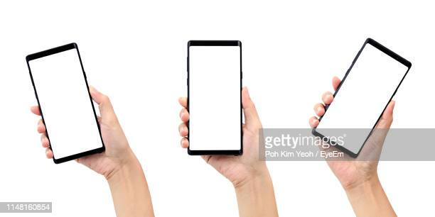 cropped hands holding mobile phones over white background - telephone stock pictures, royalty-free photos & images