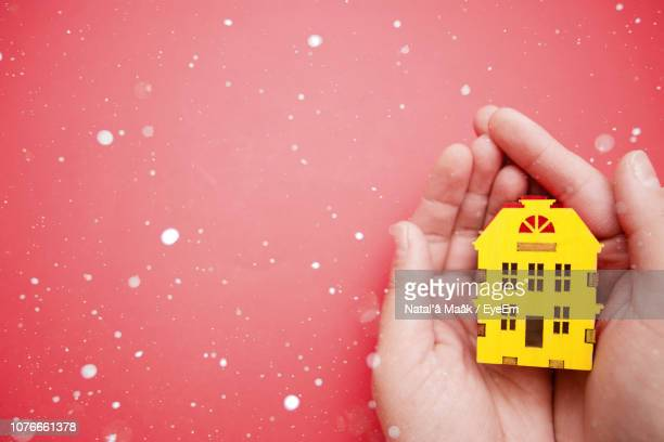 cropped hands holding model house over red background amidst snow - fake snow stock pictures, royalty-free photos & images