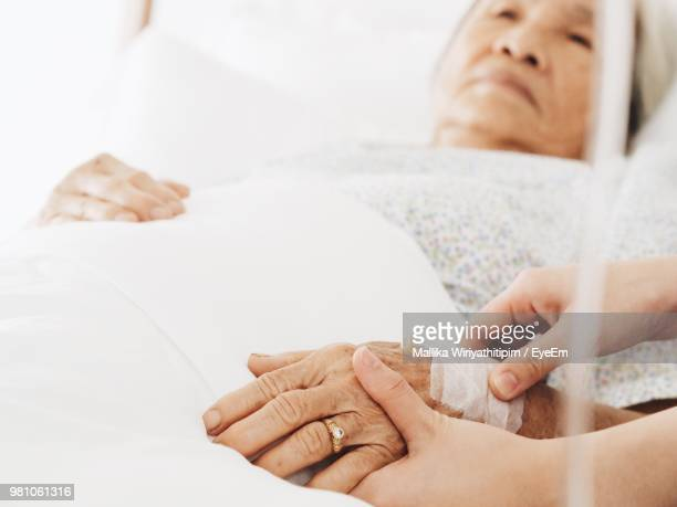 Cropped Hands Holding Patient At Hospital