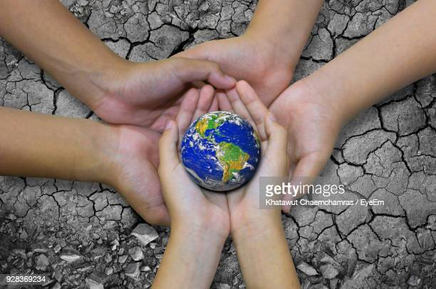 cropped hands holding planet earth - klima stock-fotos und bilder