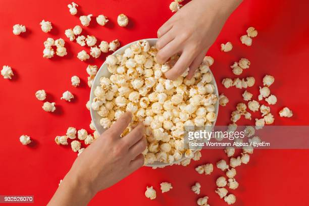 cropped hands holding popcorns in bowl over red background - menselijk lichaamsdeel stockfoto's en -beelden