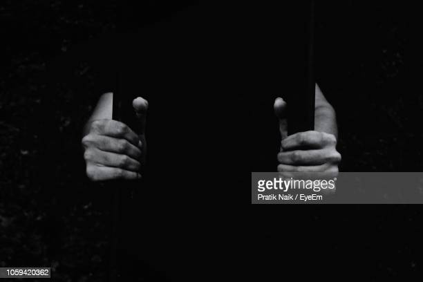 cropped hands holding prison bars - penalty stock pictures, royalty-free photos & images