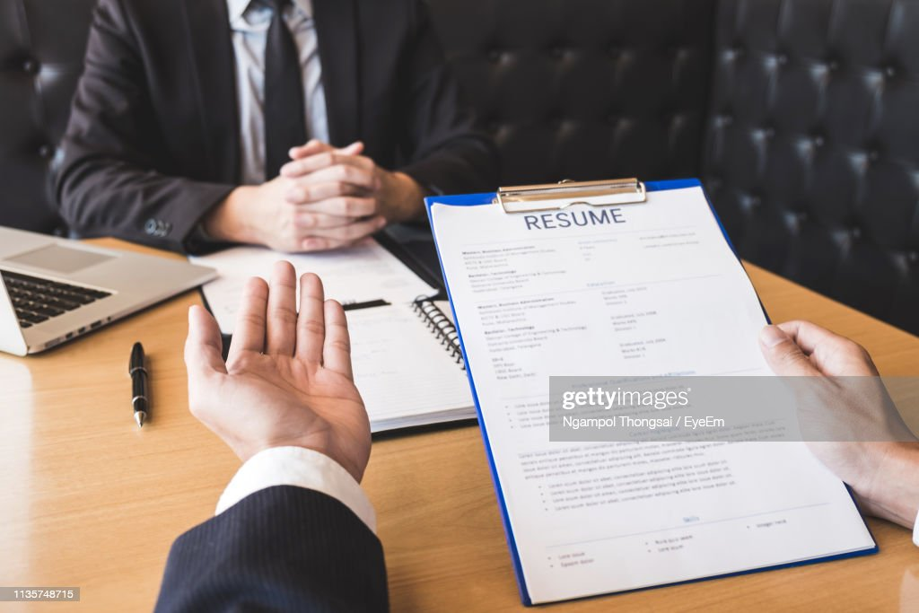 Cropped Hands Holding Resume Of Candidate : Stock Photo