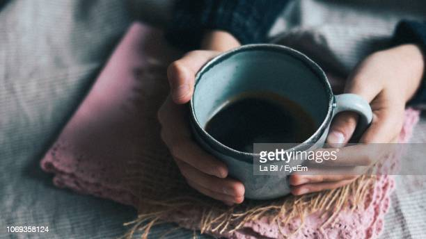 cropped hands holding tea cup on table - herbal tea stock pictures, royalty-free photos & images