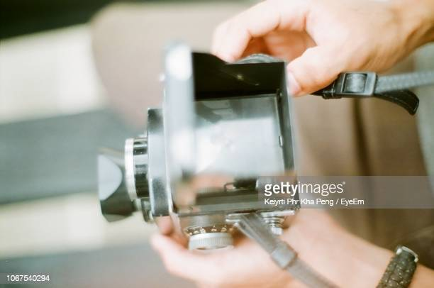 cropped hands holding vintage camera - photographic film camera stock photos and pictures