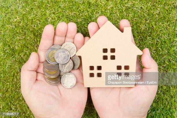 Cropped Hands Holding Wooden House Toy With Coins Over Grassy Field