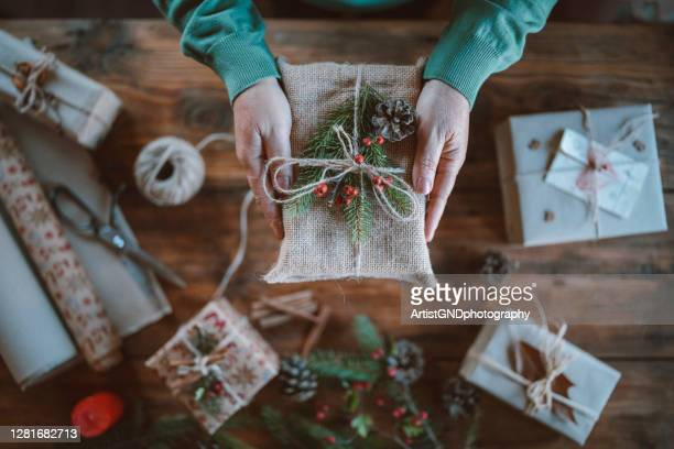 cropped hands holding wrapped christmas gift - giving tuesday stock pictures, royalty-free photos & images