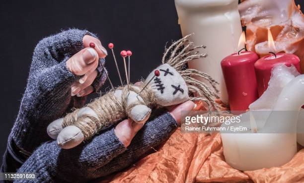 cropped hands inserting straight pin in voodoo doll - voodoo doll stock photos and pictures