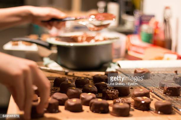 cropped hands making chocolate cake in kitchen - chocolate making stock pictures, royalty-free photos & images