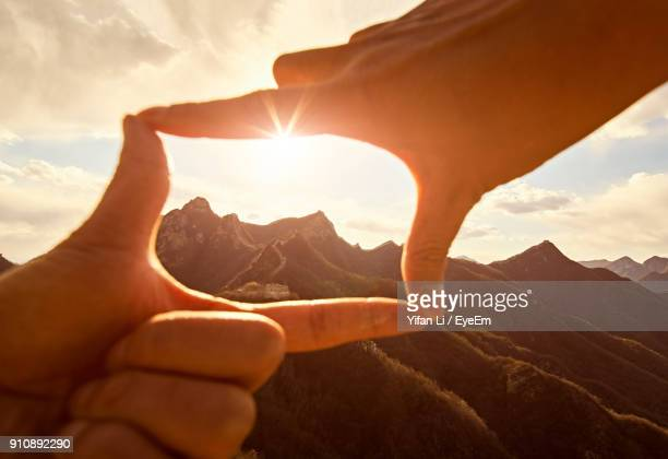 cropped hands making frame against great wall of china during sunset - parte de imagens e fotografias de stock