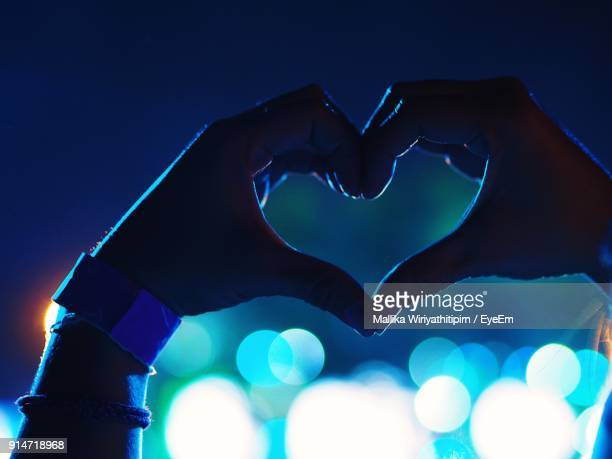 Cropped Hands Making Heart Shape Against Illuminated Lights