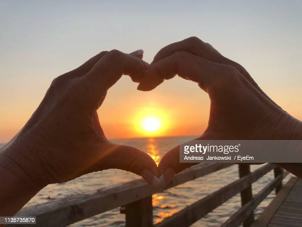 cropped hands making heart shape against sun during sunset - andreas solar stock pictures, royalty-free photos & images