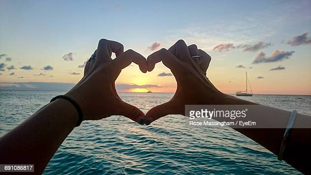 Cropped Hands Making Heart Shape By Sea Against Sky During Sunset
