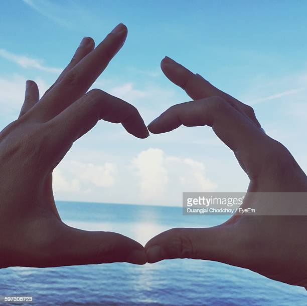 Cropped Hands Making Heart Shape By Sea Against Sky