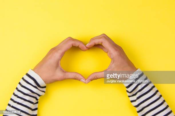 Cropped Hands Making Heart Shape Over Yellow Background