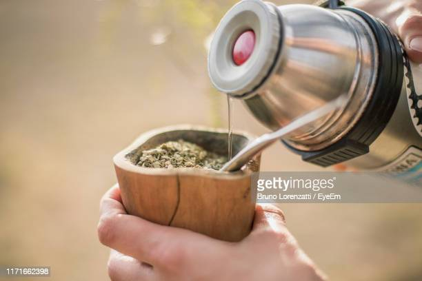 cropped hands making yerba mate tea in wooden cup - argentina stock pictures, royalty-free photos & images