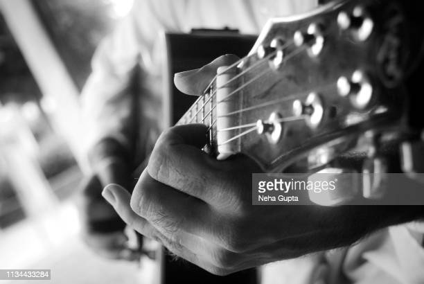 cropped hands of a man playing an acoustic guitar - countrymusik bildbanksfoton och bilder