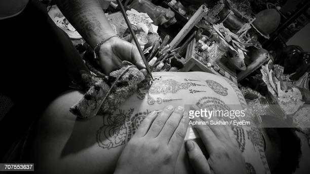 Cropped Hands Of Artists Making Tattoo On Back Of Man
