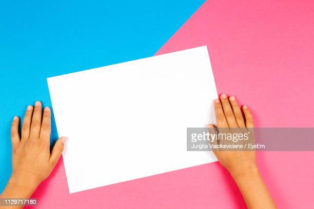 cropped hands of boy holding blank paper over colored background - two tone color stock pictures, royalty-free photos & images
