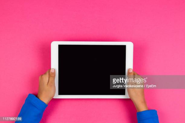 cropped hands of boy holding digital tablet over colored background - digital tablet stock pictures, royalty-free photos & images