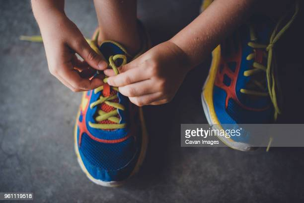 cropped hands of boy tying shoelace - tie stock pictures, royalty-free photos & images