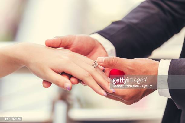cropped hands of bridegroom putting ring in bride - wedding ring stock pictures, royalty-free photos & images