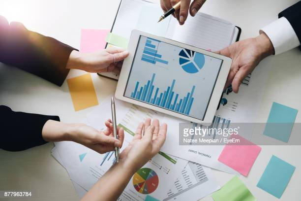 cropped hands of business people using digital tablet at office - diagram stock pictures, royalty-free photos & images