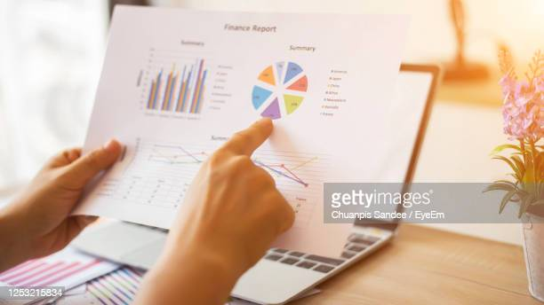 cropped hands of business person analyzing graph in office - report document ストックフォトと画像