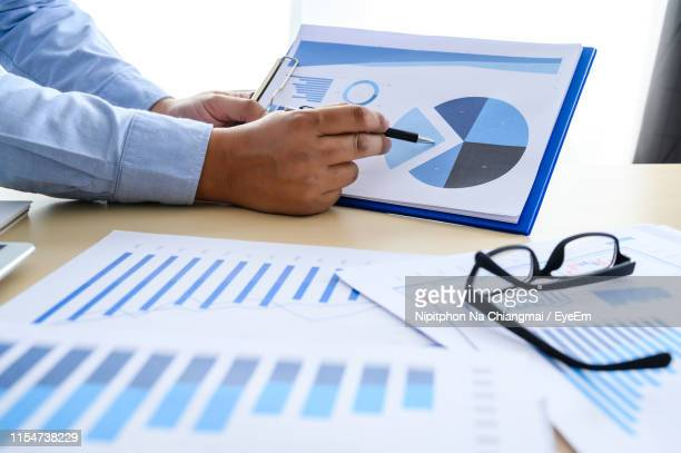 cropped hands of business person working over graph in office - pie chart stock pictures, royalty-free photos & images