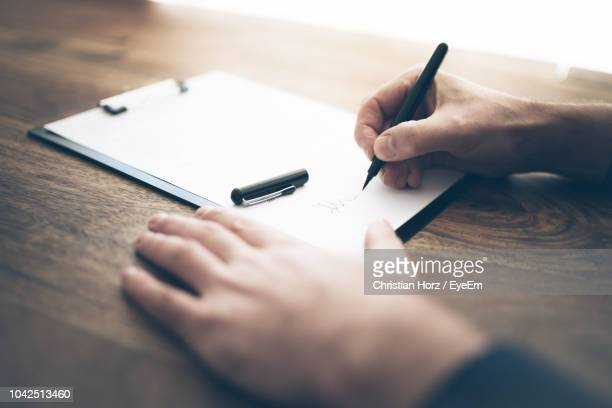 cropped hands of businessman filling form on office desk - parte do corpo humano imagens e fotografias de stock