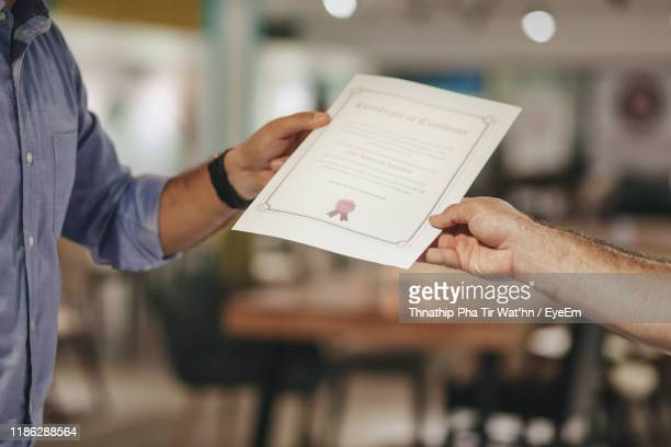 cropped hands of businessman holding certificate - certificate stock pictures, royalty-free photos & images