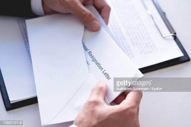 cropped hands of businessman holding resignation letter - quitting a job stock pictures, royalty-free photos & images