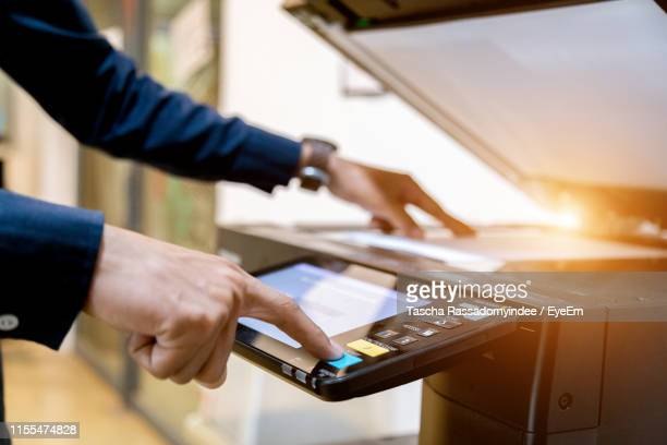 cropped hands of businessman making copies in office - copying stock pictures, royalty-free photos & images