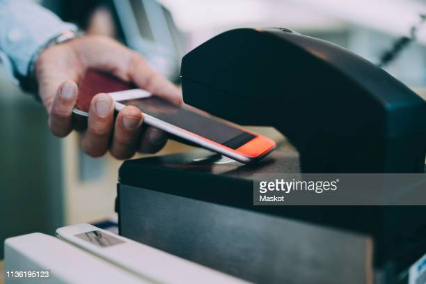 cropped hands of businessman scanning ticket on smart phone at airport check-in counter - kiosk stock pictures, royalty-free photos & images
