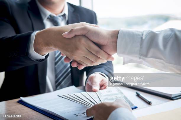 cropped hands of businessman shaking hands while bribing coworker in office - corruption stock pictures, royalty-free photos & images