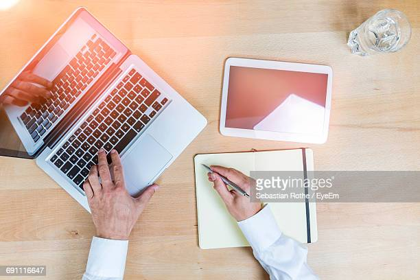 Cropped Hands Of Businessman Typing While Writing In Notepad On Desk At Office