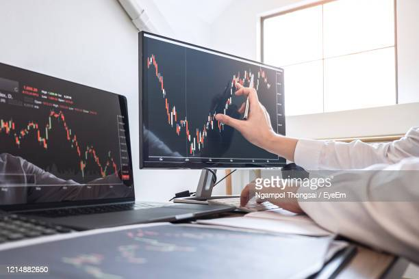 cropped hands of businesswoman analyzing stock market data over computer in office - trading stock pictures, royalty-free photos & images